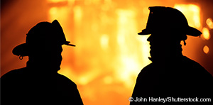 silhouette of first responders by fire